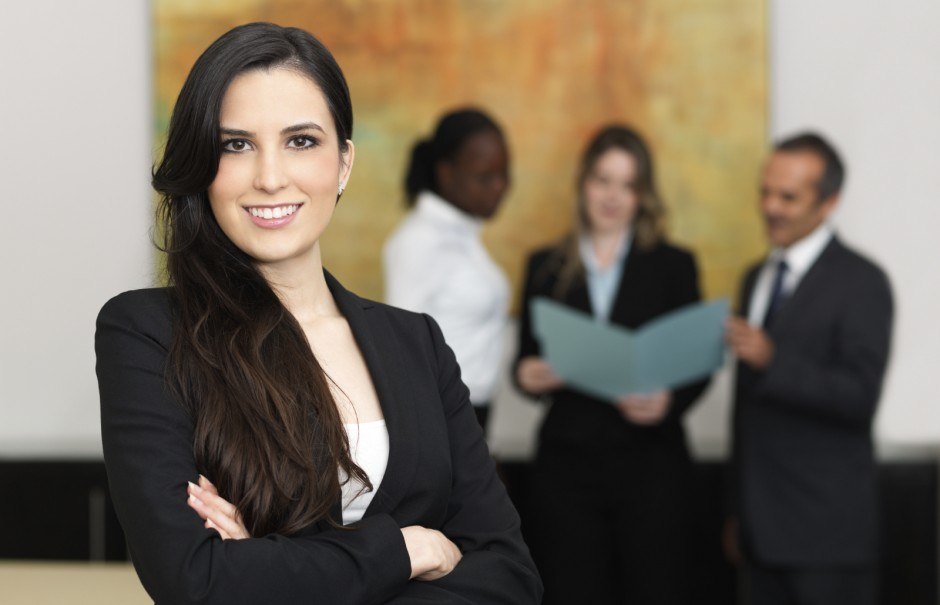 Confident-business-woman-with-her-team_iS-16547750-940x605